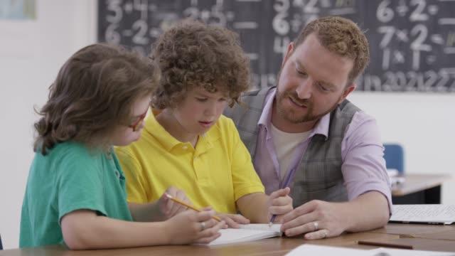 vídeos de stock, filmes e b-roll de professor, olhando para as pastas de trabalho - surdo