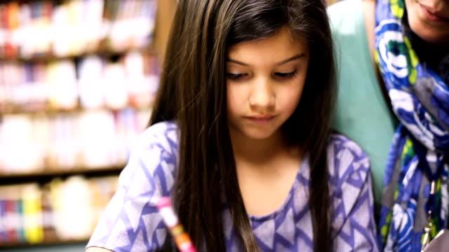 Maestro, mentor ayuda a colegiala de edad de escuela primaria con la tarea. - vídeo