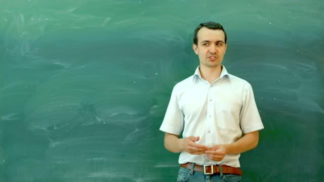 Profesor junto a la pizarra en blanco, pizarra en clase - vídeo