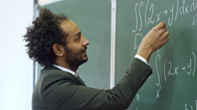 vídeos y material grabado en eventos de stock de profesor de cálculo explicar ecuaciones en conferencia - clase de matemática