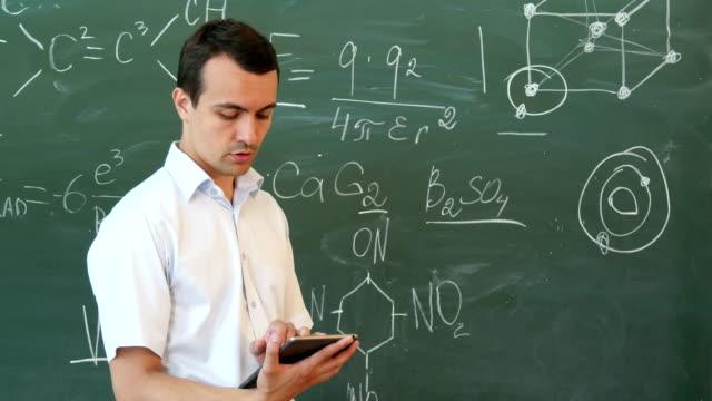 Leraar scheikunde toonaangevende Hoorcollege uit tablet staan voor het bord video