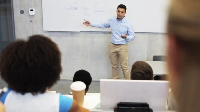 professeur ou chargé de cours au tableau blanc dans la salle de conférence - Vidéo