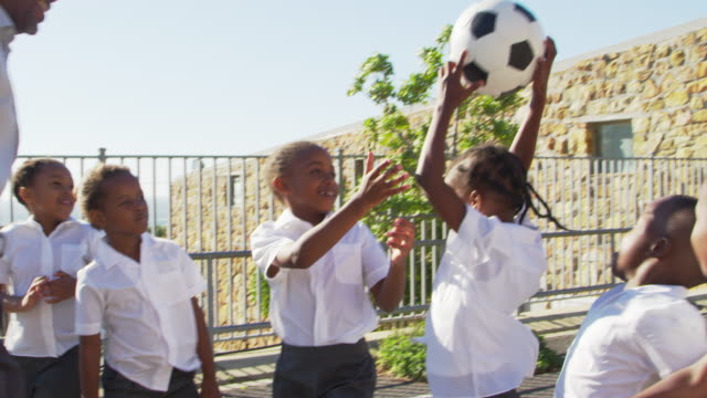 teacher passes football to young kids in school playground - bambine africa video stock e b–roll