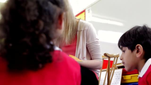 教師リーティングストーリーを小学校 pupils - 制服点の映像素材/bロール