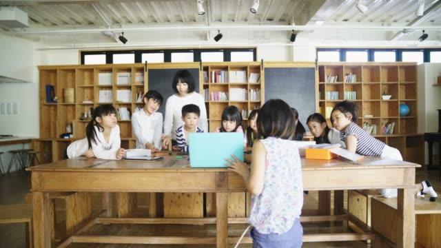 技術レッスン中にラップトップ上先生を示す学生情報 - パソコン 日本人点の映像素材/bロール