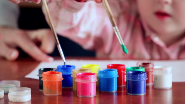 Lärare visar för flickan regler för ritning gouache i konst skola video