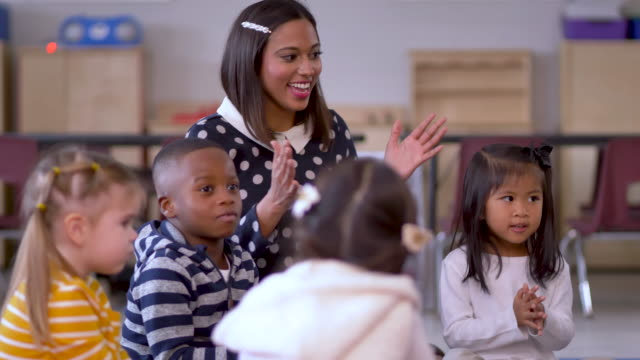 Teacher sings and claps with children. A diverse group of preschool children and their teacher sitting on the floor clapping and singing child care stock videos & royalty-free footage