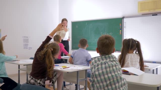 stockvideo's en b-roll-footage met docent staat vooraan in klasse in de buurt van blackboard en leerlingen vraagt vraag waarnaar ze hun handen te verhogen - schooljongen