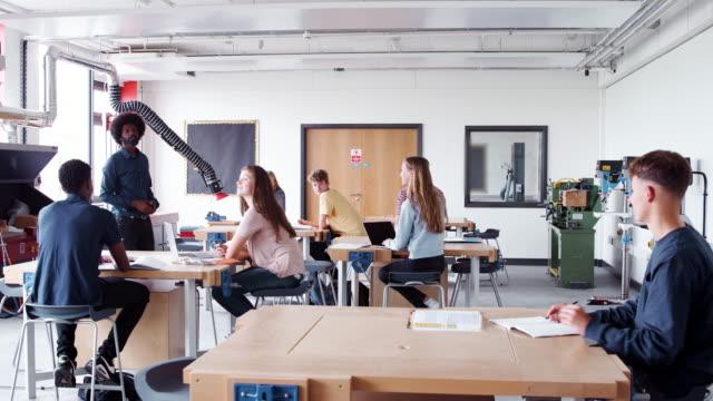 디자인 및 기술 수업에서 작업 벤치에 앉아 하는 고 등 학생의 그룹에 얘기 하는 교사 - 와이드 샷 스톡 비디오 및 b-롤 화면