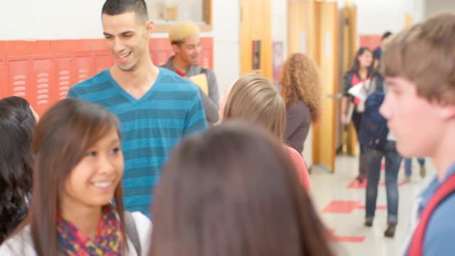 Teacher talks with student -Uberstock- HD 1080p-  High school teacher walks down hallway talking with students.  Medium shot.  locker stock videos & royalty-free footage