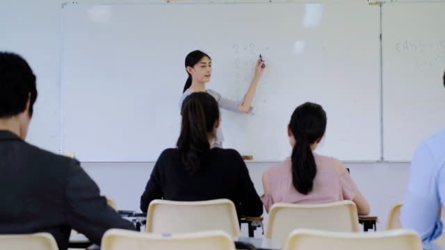 Teacher teaches students on board.education, high school, university, teaching and people concept. video