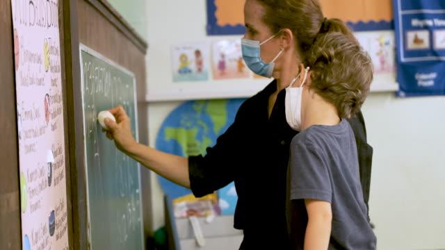 vídeos y material grabado en eventos de stock de maestro enseñando a un estudiante de preescolar ambos usando máscaras protectoras en el salón de clases - cuidado infantil