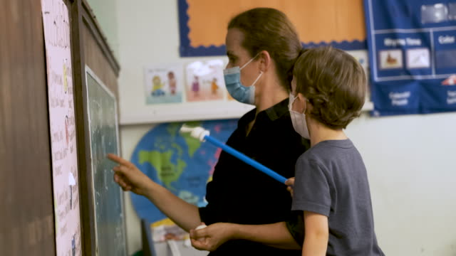 Teacher teaching a pre school schoolboy Both wearing protective face masks in the classroom