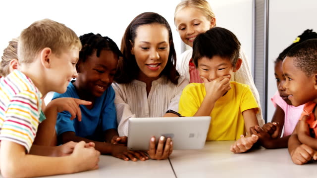 Teacher teaching school kids on digital tablet in classroom
