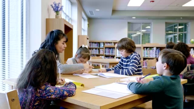 Teacher tutors group of students after school Mature Hispanic female teacher helps a group of elementary school students after school with homework assignments. elementary age stock videos & royalty-free footage