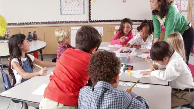 vídeos y material grabado en eventos de stock de profesor usa bloques clase de jóvenes con los niños, toma en r3d - escuela primaria