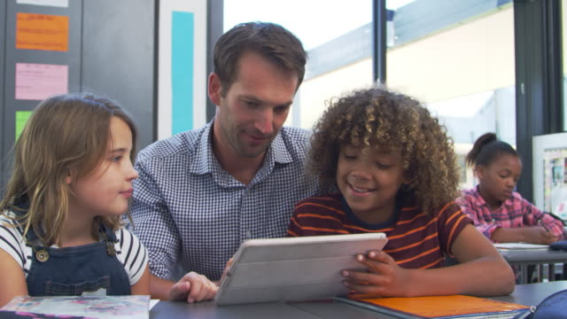 Teacher using tablet with two kids in elementary class video