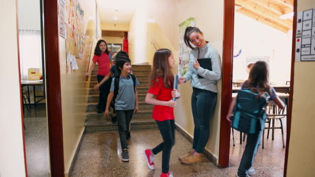 Teacher welcoming students in classroom Teacher stands at the corridor and welcomes students in classroom elementary age stock videos & royalty-free footage
