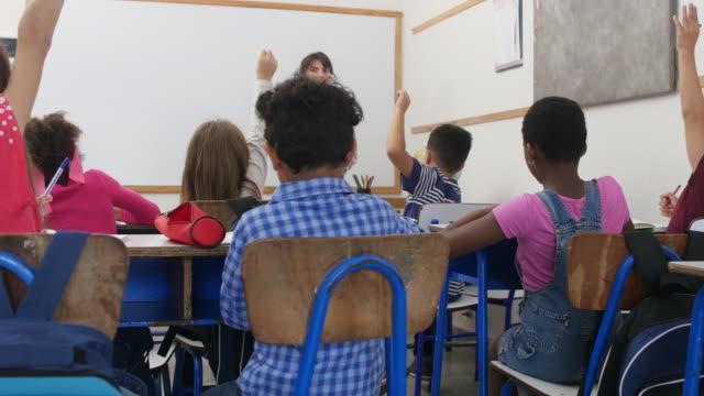 insegnante con appunti che chiedono agli studenti a scuola - argentina america del sud video stock e b–roll