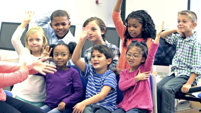 Teacher with elementary school students raising hands video