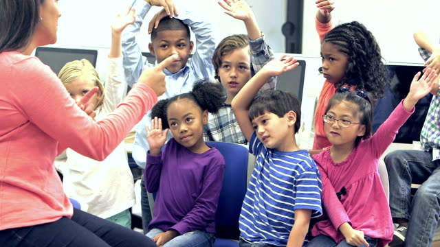 Teacher with elementary school students raising hands video