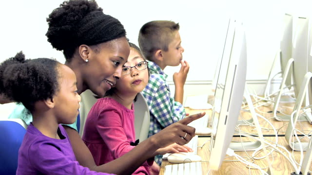 Teacher with elementary school students using computers video