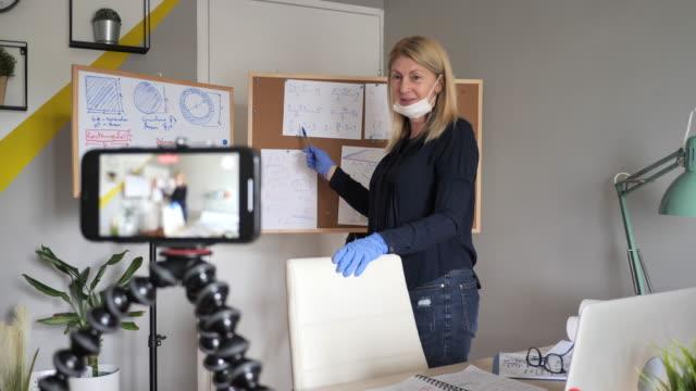 stockvideo's en b-roll-footage met leraar met gezichtsmasker en beschermende handschoenen die wiskunde op e-het leren platform verklaren - onderwijzen