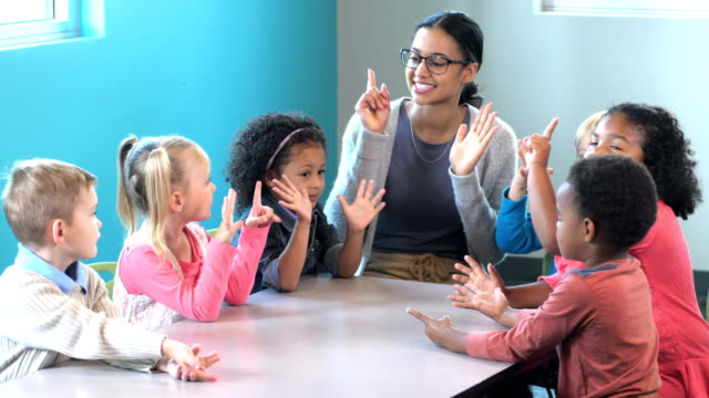 Teacher with preschool students, counting on fingers A young mixed race African-American and Caucasian woman teaching a multi-ethnic group of 4 year old preschool boys and girls. They are holding up their hands, counting on their fingers. child care stock videos & royalty-free footage
