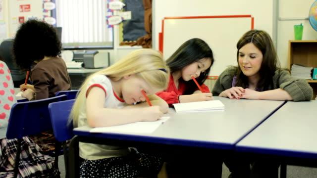 dolly: teacher with pupils - çalışma kitabı stok videoları ve detay görüntü çekimi