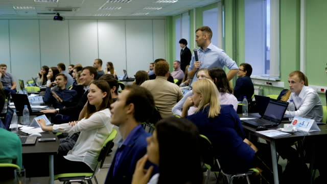 Teacher with the students look at the picture from the projector and analyze financial informationon a lesson on the economics. University speaker uses a microphone in their lessons video