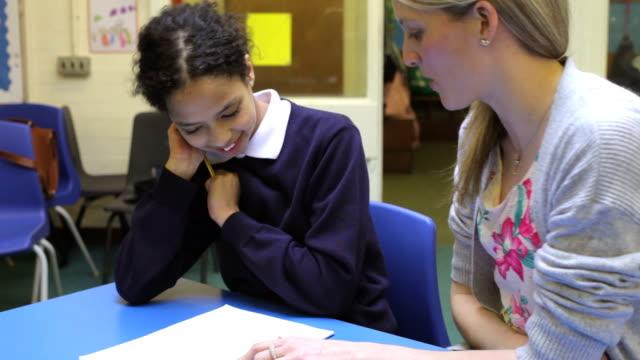 Lehrer arbeiten mit weiblichen Schüler am Schreibtisch – Video