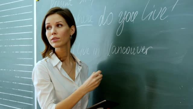Teacher writing on the blackboard video