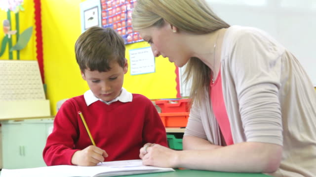 Teacher Writing With Male Pupil At Desk video