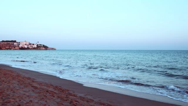 Sarcelle et orange vue au coucher du soleil sur une plage de sable sur la Costa dorada, Espagne. - Vidéo