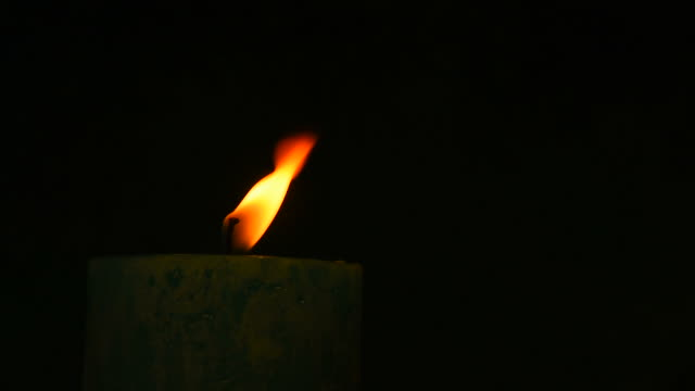 Teal candle trembling flame out of the dark blown out video
