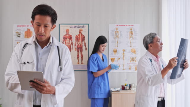 Team a doctor working inside the examination room by using the tablet X-ray film And Medical Devices