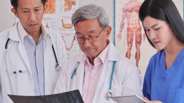 錠剤x線フィルムと医療機器を使用して検査室内で働く医師をチーム化 - 心臓点の映像素材/bロール