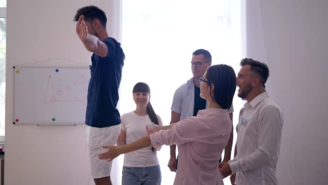 team building, young man on chair falls down on back trusting his colleagues that they catch him - fiducia video stock e b–roll