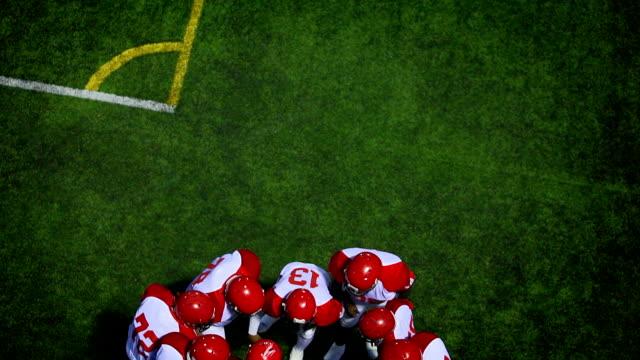 Team huddles on field together