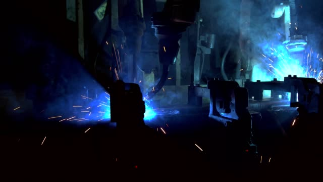 team industrial robots are welding in factory - telecomando background video stock e b–roll
