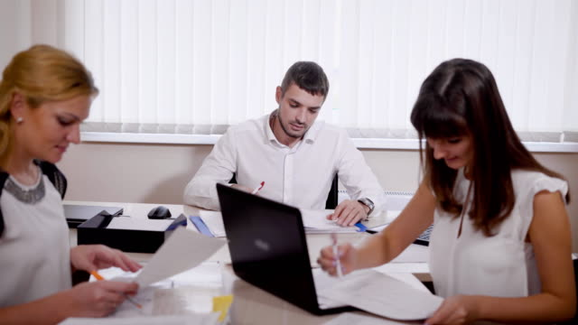 vídeos de stock, filmes e b-roll de equipe de trabalho de contabilistas têm uma discussão sobre documentos - assistente jurídico