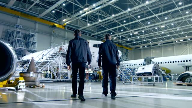 vídeos de stock, filmes e b-roll de equipe de mecânica de aeronaves e engenheiros acordar através de avião de manutenção, design e desenvolvimento facilidade. profissionais que prendem ferramentas e equipamento de reparo - manufaturando