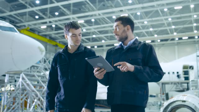 Team of Aircraft Mechanics and Engineers Waking Through Airplane Maintenance, Design and Development Facility. Professionals Consulting Digital Tablet Computer and Talking