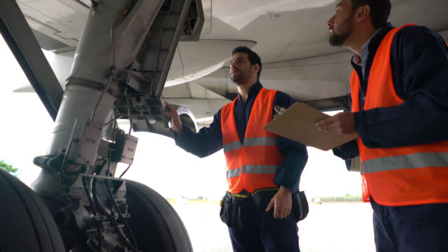 Team of airplane mechanics checking the landing gear of an airplane one points at parts and the other one takes notes
