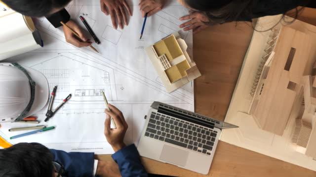 slo-mo-team von architekten, die brainstorming-design-lösungen - konferenztisch stock-videos und b-roll-filmmaterial