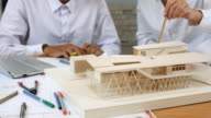 istock Team of Architects defining detail of architectural model in office 637325802