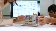 istock Team of Architects defining detail of architectural model in office 637328160