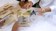 istock Team of Architects defining detail of architectural model in office 637336396