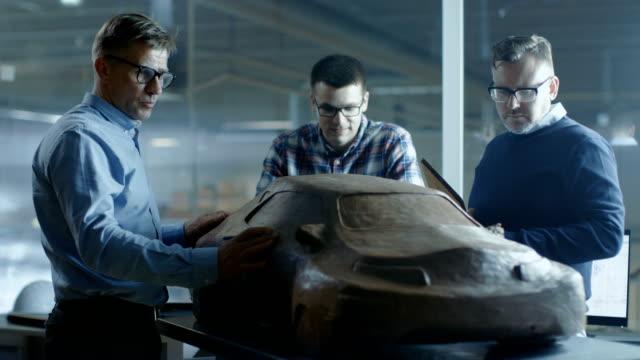 vídeos y material grabado en eventos de stock de equipo de ingenieros de diseño automotriz analiza nuevo modelo de prototipo de arcilla plastilina. trabajan en una fábrica de coches grandes. - montar