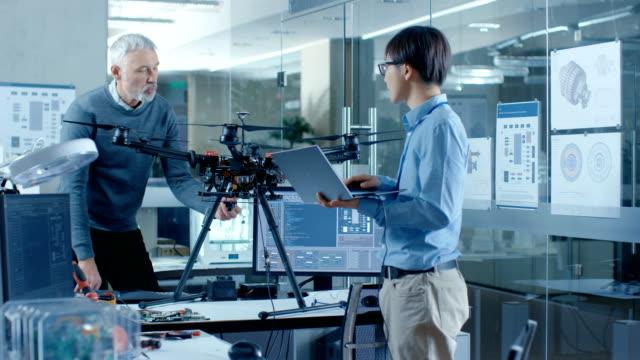 vídeos de stock, filmes e b-roll de equipe de trabalho de engenheiros de aviação em uma aeronave nova, tem discussão, uso portátil. no laboratório científico de fundo. - avião sem piloto